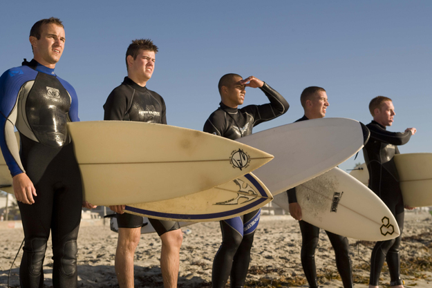 Cadets holding surfboards at waterfront